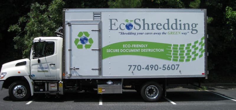 EcoShedding mobile shredding truck in parking lot in front of trees